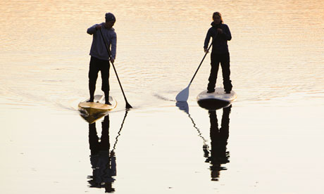 Two people rowing paddle boards in water at dusk